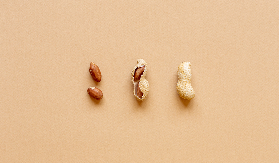 3 peanuts on beige background