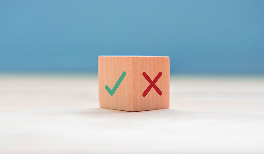 Green checkmark and red X on wooden die