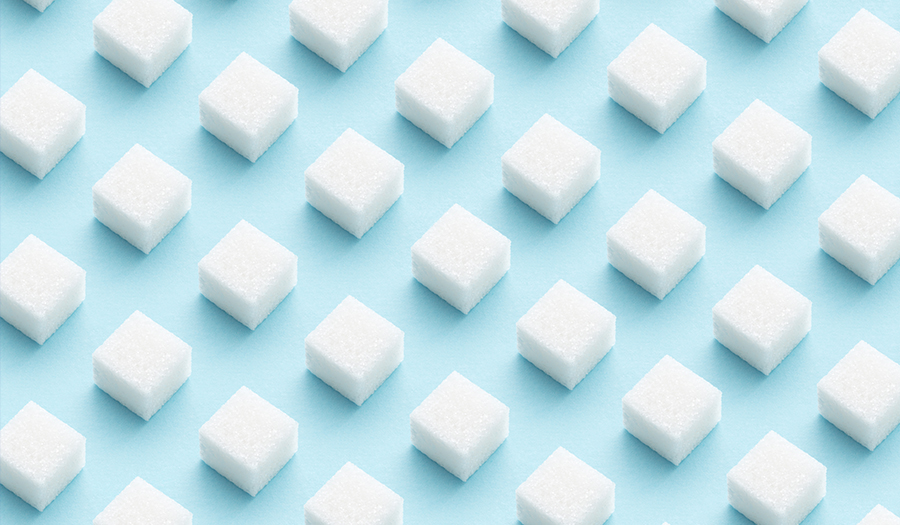 Pattern made of sugar cubes on blue background