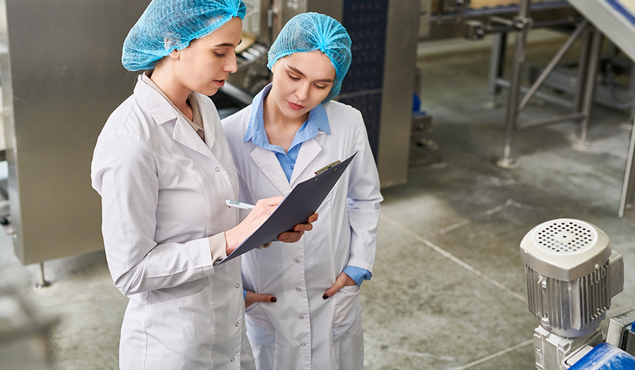 Two factory worker women in hairnets looking at clipboard on plant floor