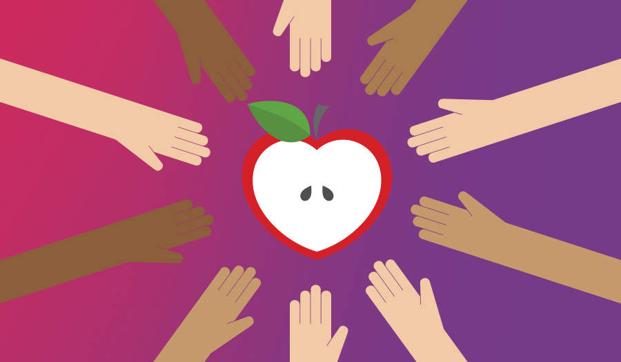 Children's hands reaching out to apple shaped like a heart