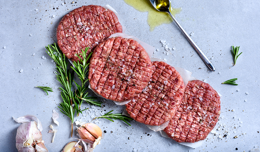 Seasoned ground meat patties with thyme sprigs, garlic cloves, sea salt, and olive oil