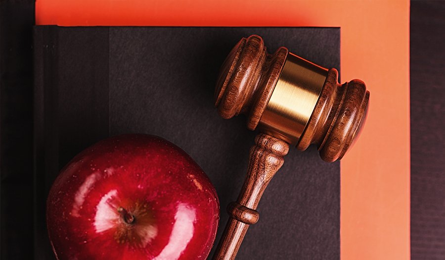 Gavel with red apple