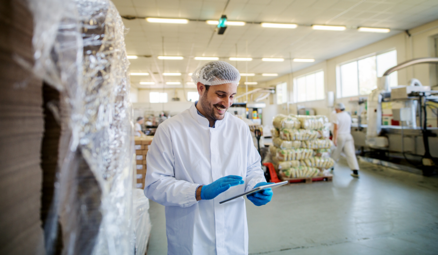Young male manager in sterile clothes standing in food factory and looking at tablet