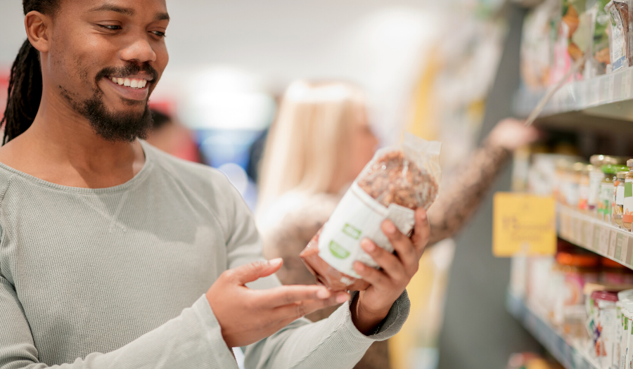 man looking at bread label in grocery store