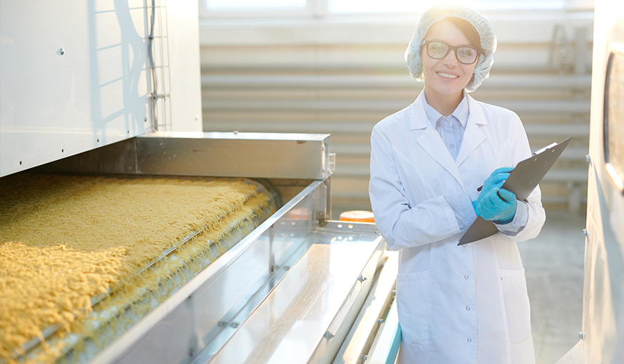 Young woman posing at factory in sunlight standing by macaroni conveyor belt